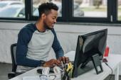 bello programmatore africano americano che lavora al computer in ufficio