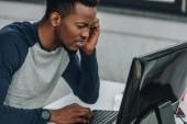 Fotografia dispiaciuto programmatore afroamericano guardando monitor del computer in ufficio