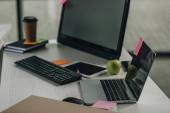 Schreibtisch mit Laptop, Computermonitor, Tastatur und digitalem Tablet im Büro