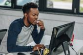 Fotografia concentrato programmatore africano americano che lavora al computer in ufficio