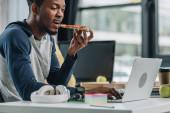 mladý Afričan americký programátor konzumní pizzu při práci v kanceláři