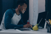 Fotografie cheerful african american programmer working at night in office