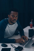 Fotografia grave programmatore africano americano guardando la fotocamera mentre si lavora di notte in ufficio