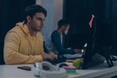 selektivní zaměření vážného programátora při pohledu na monitor při práci v noci u afrického přítele