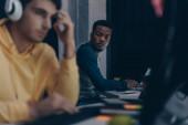 focus selettivo del programmatore africano americano guardando collega in cuffia