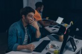 Fotografie selective focus of surprised programmer looking at monitor while working near african american colleague