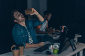 Fotografie selective focus of young programmer drinking coffee to go near african american colleague