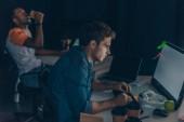 Fotografia focus selettivo di programmatore attento che lavora sul computer vicino collega americano africano bere caffè per andare