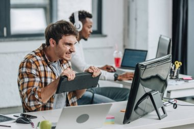 selective focus of angry programmer holding keyboard and looking at computer monitor while sitting near african american colleague in office