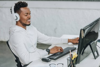 happy african american programmer sitting at workplace in headphones