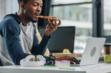 young african american programmer eating pizza while working in office