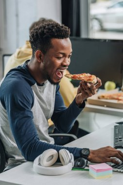 hungry african american programmer eating pizza while sitting at workplace near colleague