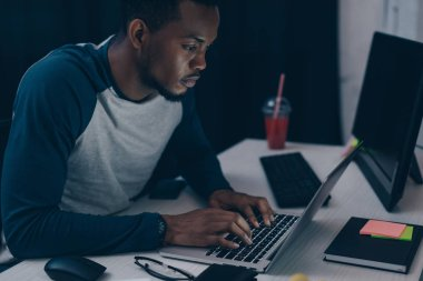 attentive african american programmer using laptop while working at night in office