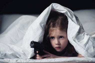 Frightened child holding gun while hiding under blanket isolated on black stock vector