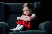 depressed, scared child sitting in armchair and looking at camera isolated on black