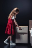 cute child in red dress opening nightstand on black background