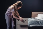 adorable child in pajamas opening nightstand isolated on black