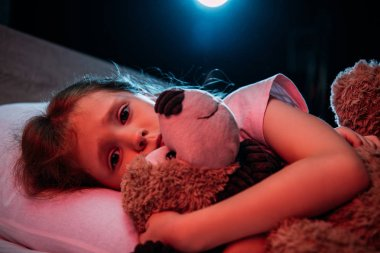 frightened child embracing teddy bear while lying in bed and looking at camera