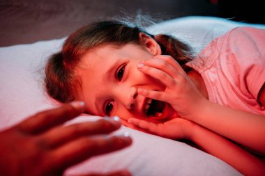 male hand near frightened, screaming child lying in bed