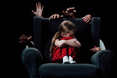 scared child sitting in armchair surrounded with human hands isolated on black