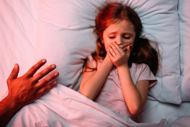 male hand near frightened child lying in bed and showing hush sign