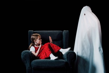 direful ghost standing near scared girl sitting in armchair isolated on black