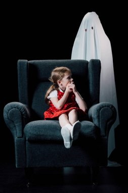 frightened child showing hush sign near white ghost standing behind armchair isolated on black