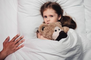cropped view of male hand near scared child lying in bed with teddy bear