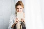 Fotografie attraktive Frau im weißen Pullover mit Decke, die Buch hält