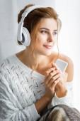 atraktivní žena v bílém svetru naslouchající hudbě a v držení smartphone