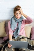 attractive and shocked woman with grey scarf holding laptop