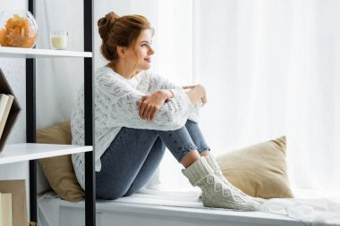 side view of attractive woman in white sweater and jeans sitting and looking away
