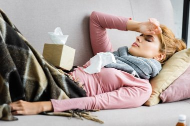 attractive and ill woman in grey scarf with headache lying in apartment