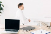 selective focus of doctor in white coat and laptop with blank screen on foreground