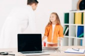 selektiver Fokus von Kinderarzt und Patient und Laptop mit leerem Bildschirm im Vordergrund