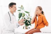 gyereket, amely száját kézzel, és mosolygós gyermeki gazdaság orvosi spatula a klinikán