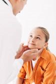 Ausgeschnittene Ansicht eines Kinderarztes im weißen Kittel, der ein Kind isoliert auf Weiß untersucht