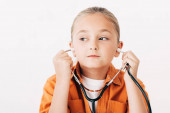 Photo pensive child holding stethscope and looking away isolated on white