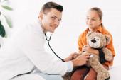 dětský a usměvavý pedilog v bílém plášti zkoumáním medvídka se stetoskoborem na klinice