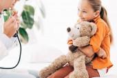 Teilansicht von Kinderarzt in weißem Mantel und Kind mit Teddybär in Klinik