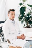Fotografia medico pensieroso in camice bianco seduto con le mani serrate