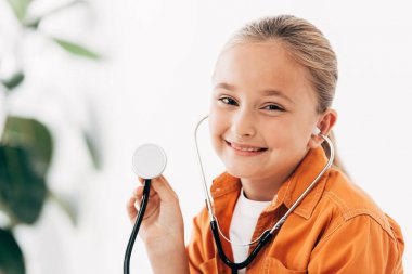 Smiling child holding stethscope and looking at camera in clinic stock vector