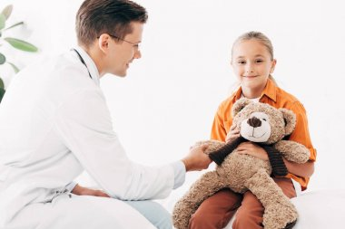 Smiling pediatrist in white coat and kid with teddy bear in clinic stock vector