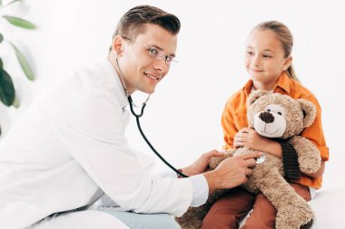 Kid and smiling pediatrist in white coat examining teddy bear with stethoscope in clinic stock vector