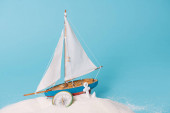 Photo decorative ship near anchor and compass in white sand on blue background
