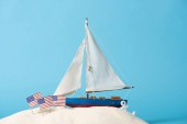 Photo decorative ship near American national flags in white sand isolated on blue