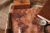 Photo wooden box, telescope, compass and aged world map on hessian