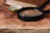 Photo close up view of magnifying glass near compass on aged world map