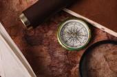 pohled na kompas blízko kopírované knihy a zvětšovací sklo na staré mapě světa