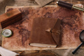 Fotografie brown leather notebook on wooden table with world map and sacking
